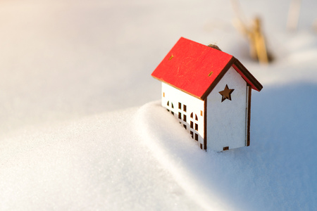 Protecting and isolating house. House model at snow background. Winter. Preparing the house for winter time. Real estate and property concept. Copy space.