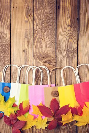 Autumn sale. Color shopping paper bags and fallen leaves on wooden background. Фото со стока