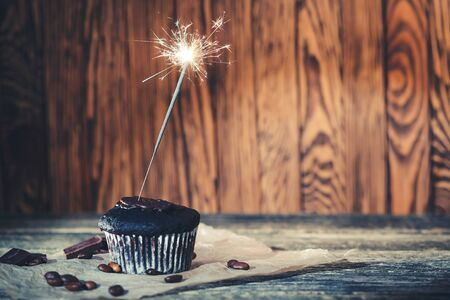 Tasty chocolate cupcake with sparkler on wooden background. Фото со стока