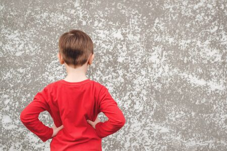 Back view of happy kid looking at grey wall with copy space. Gray concrete wall background. Mockup