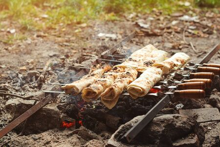 Picnic time with cooking pita bread. Lavash on the grill. Stuffed pita on the grill at nature