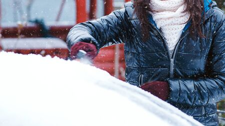 Girl cleaning car from snow. Clean car window from snow. Winter windshield car cleaning. Removing snow from window. Фото со стока