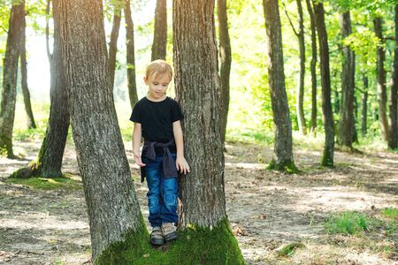 Happy boy discovering nature. Joyful child playing on the park at sunny day. Happy little boy at the forest. Family walk at wild nature. Summer holidays