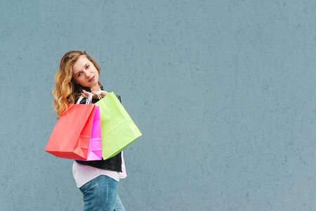 Happy girl makes purchases in an online store against a grey wall background. Copy space for text or design. Woman holding shopping bags. Seasonal sales