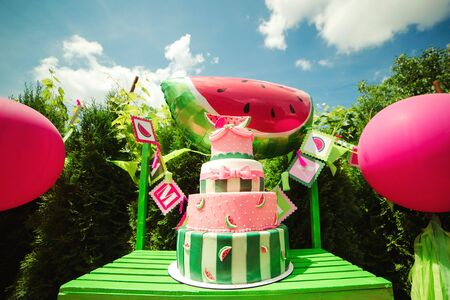 Big birthday cake on a sweet table in backyard. Family celebrating a childs birthday outdoors. Summer party for daughter Фото со стока