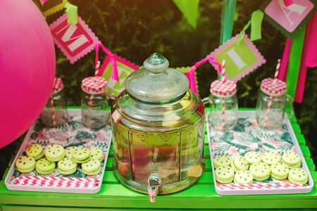 Colorful french macaroons for the birthday party. Summer outdoors party. Sweet dessert table at backyard. Summer candy bar. Big jar of lemonade