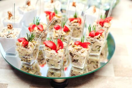 Small glasses with fresh salads at party. Catering food, snacks with salad and small tomatoes. Banquet service Stock Photo