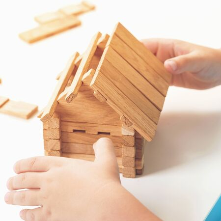 Toy wooden house. Child builds small house. Dream about home. Small model of house from wooden blocks Фото со стока
