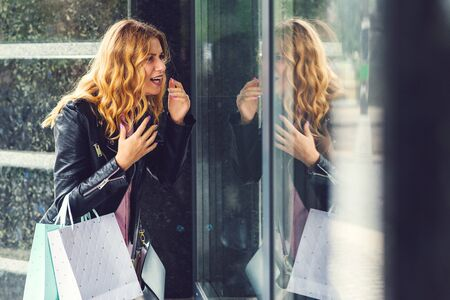 Excited stylish woman looking in shop window. Girl holding shopping bags. Black fridays concept. Seasonal sales and great discounts. Shopaholic woman.