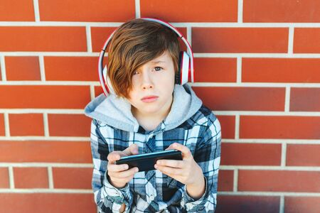 Stylish schoolboy with smartphone and headphones listening to music or playing game over brick wall. Leisure, children, technology and people concept. Imagens