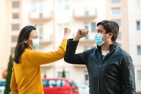 Friends shaking elbows outdoors. People maintain social distancing to prevent from virus spreading. Couple greeting with elbows. Coronavirus epidemic. Coronavirus quarantine. World global pandemic. Stock fotó