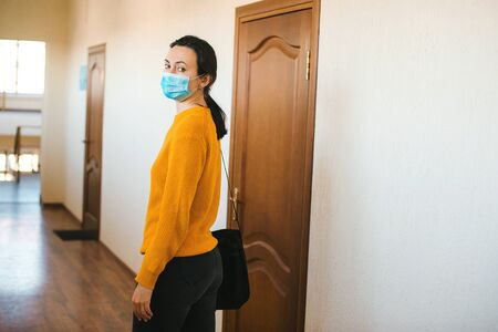 Coronavirus quarantine. Closing office during coronavirus epidemic. Woman with face mask going home. Global pandemic. Stay at home. Work from home during coronavirus quarantine. Stock Photo