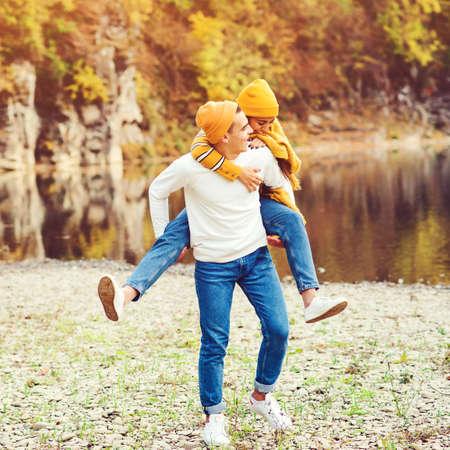 Boyfriend carrying his girlfriend on piggyback. Couple walking near lake in autumn. Fashion, lifestyle and autmn mood. Lovely couple having fun together in nature. Fashion couple enjoying autumn.
