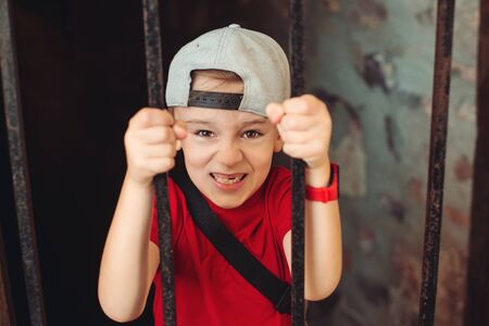 Little boy behind iron bars. Kid on an excursion in an old castle. Schoolboy in old prison tunnel. Summer holidays, camp. Abstract idea home quarantine. Global pandemic, home isolation concept. Stock Photo