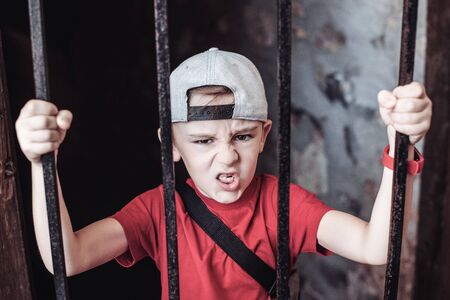 Little boy behind iron bars. Kid on an excursion in an old castle. Schoolboy in old prison tunnel. Summer holidays, camp. Abstract idea home quarantine. Global pandemic, home isolation concept.