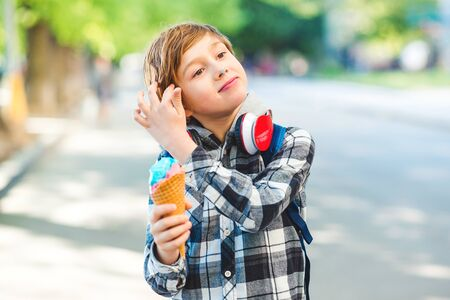 Happy boy eating ice cream outdoors. Kid walking at park in sunny day. Stylish boy outdoors. Tasty ice cream. Summer vacation. Lifestyle, fashion and vacation