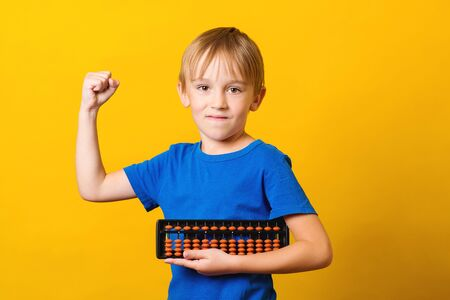 Schoolboy with abacus over yellow background. Kid study at mental arithmetic school. Education and development concept. Mental arithmetic lessons. Back to school. Smart kid, iq.