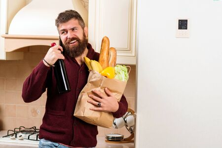 Bearded man holding bottle of wine and grocery bag. Man talking on phone at kitchen. Online shop with food, products and drinks. Delivery food, products to home. Shopping and healthy food concept.