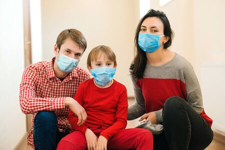 Family wearing face masks. Prevention coronavirus. Stay at home. Home quarantine. Coronavirus epidemic. Parents and kid wearing a surgical masks. Coronavirus outbreak. New real life.