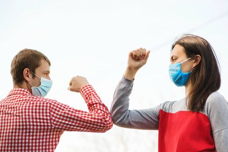 Young couple wear face masks outdoors. Social distancing. Friends greeting with elbows outdoors. New real life. Coronavirus quarantine. Fight coronavirus. Coronavirus epidemic. Friends in safety mask.