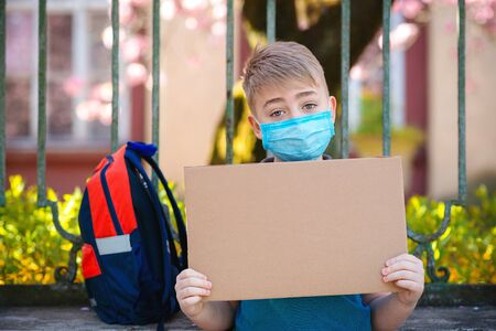Schoolboy wearing medical face mask. Student with backpack outdoors. Boy holding empty board for text. Child back to school. Coronavirus outbreak. Prevention cocoronavirus. Coronavirus quarantine.