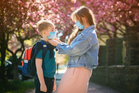 Schoolboy is ready go to school. Mother puts a safety mask on her son's face. Cute boy with a backpack outdoors. Back to school concept. Medical mask to prevent coronavirus. Coronavirus quarantine Banque d'images