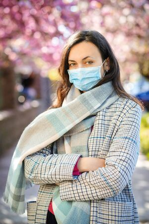 Woman wearing face mask outdoors. Safety mask to prevent coronavirus. Coronavirus world outbreak. Spring 2020. Real life during pandemic. Coronavirus prevention. Fashionable woman at street.