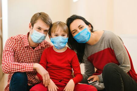 Young family in safety medical masks. Prevention coronavirus. Stay at home. Home quarantine. Coronavirus epidemic. Parents and kid wearing a surgical mask. Coronavirus outbreak. New real life.
