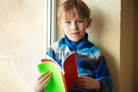 Schoolboy with books near window. Back to school. Smiling child reads book. Little student holding notebooks. Education concept. Elementary school. Pupil at school.