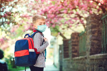 Schoolboy wearing face mask during corona virus outbreak. Boy going back to school after covid-19 quarantine. Boy in safety mask for coronavirus prevention. Kid with backpack going to school. Banque d'images