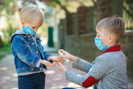Children using sanitizer for hands at city street. Cute brothers wearing face masks in spring. Kids disinfecting hands with antiseptic gel outdoors. Coronavirus outbreak. Coronavirus epidemic. Banque d'images