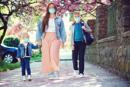 Mother and children going home during quarantine. Family wearing face masks. Springtime. Health care concept. Back to school. Education. Parent and pupil of primary school go hand in hand.