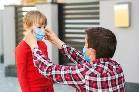 Father puts on son medical face mask outdoors. Coronavirus quarantine. Coronavirus epidemic, virus symptoms. Family wearing face mask for protection during the quarantine. Coronavirus outbreak.