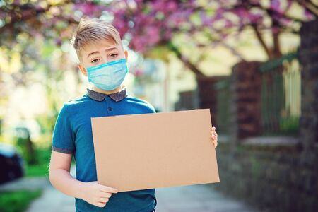 Sad kid wearing protective mask. Boy showing empty blank. Cute boy holding empty board outdoors. World global pandemic. Coronavirus epidemic. Sad boy in safety face mask.