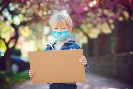 Child wearing protective mask and showing empty blank. Cute boy holding empty board with copy space outdoors. World global pandemic. Coronavirus epidemic. Banque d'images