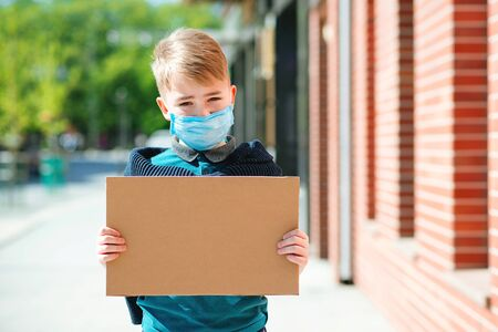 Cute boy wearing face mak. Kid holding empty board for text outdoors. Tired schoolboy need support and help. Want to school. Boy want to back to normal life. Copy space. Coronavirus world epidemic. Banque d'images