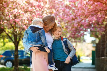 Happy mother with kids on the walk in spring city. Mother and children hugging outdoors. Happy mother's day. Family, fashion and lifestyle. Happy family. Motherhood concept.