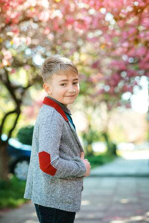 Fashionable kid in spring outdoors. Portrait of handsome young boy. Cute boy posing at city street. Kids fashion, lifestyle. Boy wearing trendy jacket, looking to camera.