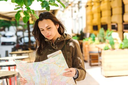 Woman traveler holding location map in hands. Sunny summer day. Girl student checking out the sights on atlas. Woman searching locations. Woman tourist studying a map at town. Travel, summer vacations.