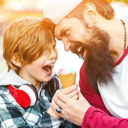Cute kid boy eating an ice cream in a cone. Father and son having fun together. Summer vacation. Tasty fruit ice cream for family. Father and son have a great time on a walk.