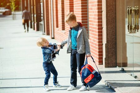 Schoolchildren with backpack going to school. Stylish brothers outdoors. Back to school concept. Friends, childhood and education. Primary school. Fashion kids on the street. Banco de Imagens