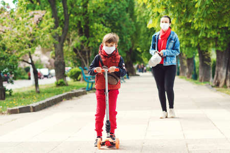 Riding boy on scooter in park. Boy wears medical face mask. Mother and son on a walk during coornavirus quarantine. Family in safety masks outdoors. Real life 2020. Coronavirus epidemic.