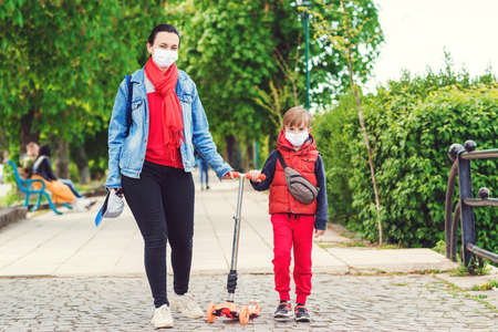 Family in safety masks outdoors. Riding boy on scooter in park. Boy wears medical face mask. Real life 2020. Coronavirus epidemic. Mother and son on a walk during coornavirus quarantine.