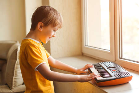 Cute boy is playing on a synthesizer at home. Children's piano. Development of musical abilities in children. Creative kid having fun during quarantine. Kids hobbies and leisure. Stay home. Quarantine