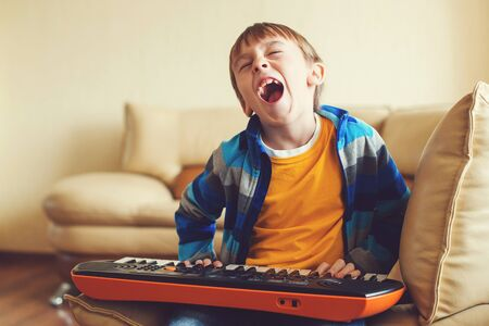 Cute schoolboy playing on synthesizer at home. Children's piano. Development of musical abilities in children. Kids hobby and leisure. Boy learning to play musical instruments.
