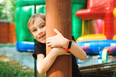 Cute boy plays in adventure park. Summer camp, vacations. Happy child having fun in outdoors playground. Happy childhood.