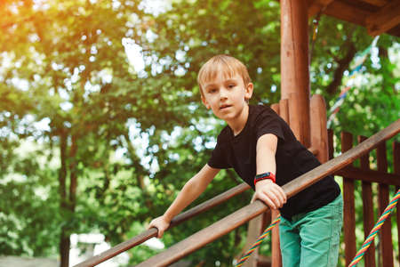 Cute kid playing in a tree house. Summer vacations, travel and leisure. Happy boy having fun at summer park. Adventure park for kids. Boy in a treehouse outdoors. Banque d'images