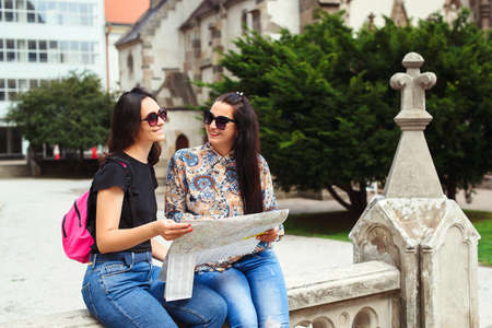 Young happy friends sightseeing in city. Friendship and travel concept. Two women reading map on the street. Fashionable girls walking in Europe modern city centre. Travle, lifestyle, vacations.