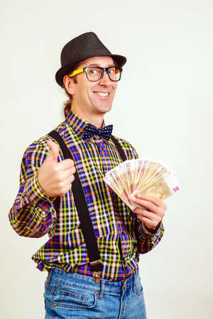 Nerd man with fan of money. Man gesturing thumb up. Successful guy with cash money. Isolated on white wall. Winner, lottery and savings concept.