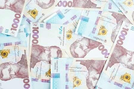 Ukrainian money background. 1000 hryvnia banknotes. Ukrainian inflation and economical crisis. Exchange rate. Cash money, top view.